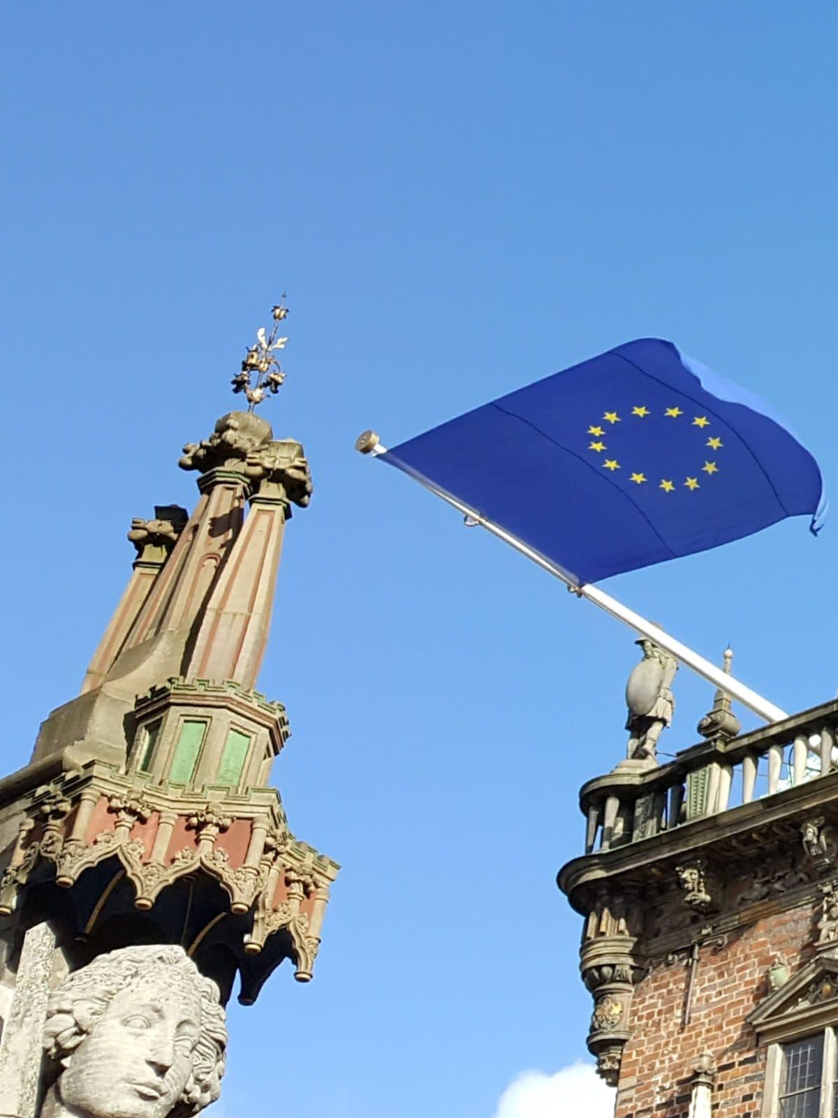 Der Kopf der Rolandstatue in Bremen neben der Europaflagge am Rathaus